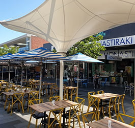 Outdoor dining area in Cafe zone in Eaton Mall Oakleigh. Tables and chairs sited under fixed and temporary umbrella shelters.