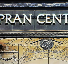 Signage above an entry to Pran Central Shopping Centre in Prahran. Sign sits above ornate ironwork which supports the sign.